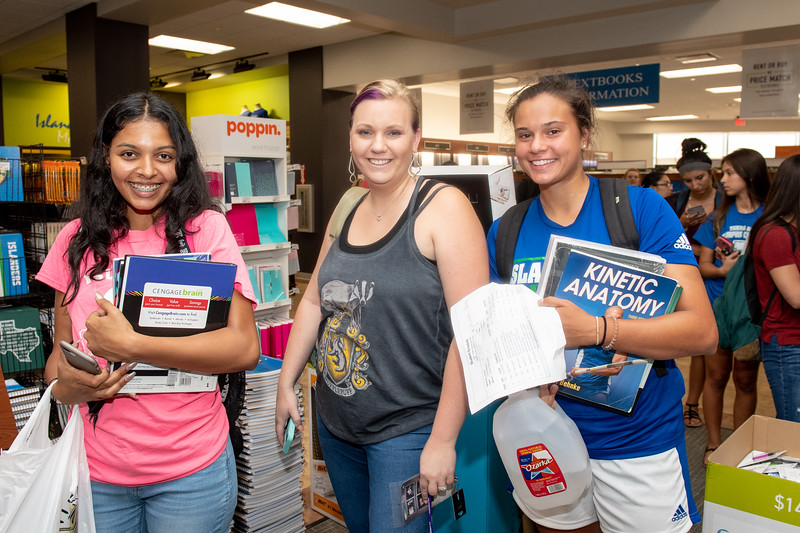 Kaila Jameson (left), Megan Hill, and Madeline Lozano pick up their books from the Barnes and Noble store on campus.