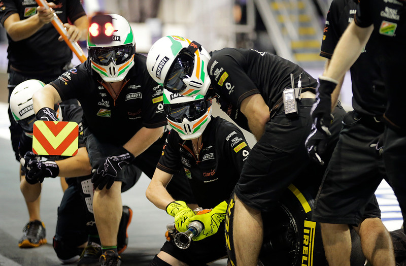 . Mechanics from team Force India prepare for a tire change during the second practice session for the Singapore Formula One Grand Prix on the Marina Bay City Circuit in Singapore, Saturday, Sept. 20, 2014. (AP Photo/Wong Maye-E)