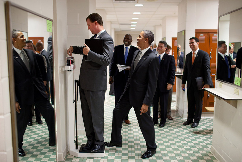 ". Aug. 8, 2010 ""We were walking through a locker room at the University of Texas when White House Trip Director Marvin Nicholson stopped to weigh himself on a scale. Unbeknownst to him, the President was stepping on the back of the scale, as Marvin continued to slide the scale lever. Everyone but Marvin was in on the joke.\"" (Official White House Photo by Pete Souza)"
