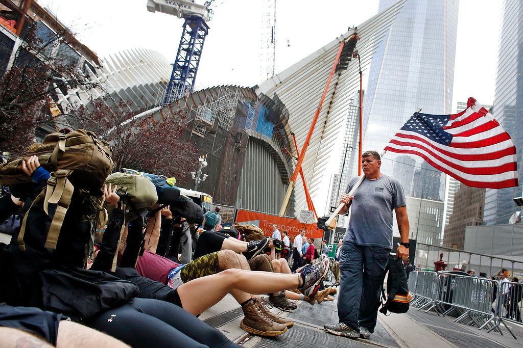 . United States Marine Corps veteran John Croft, right, leads a group of athletes through calisthenics at the end of the GORUCK 9/11 Tribute Challenge, a few blocks from 1 World Trade Center on the 13th anniversary of the Sept. 11, 2001 attacks, Thursday, Sept. 11, 2014, in New York. (AP Photo/Jason DeCrow)