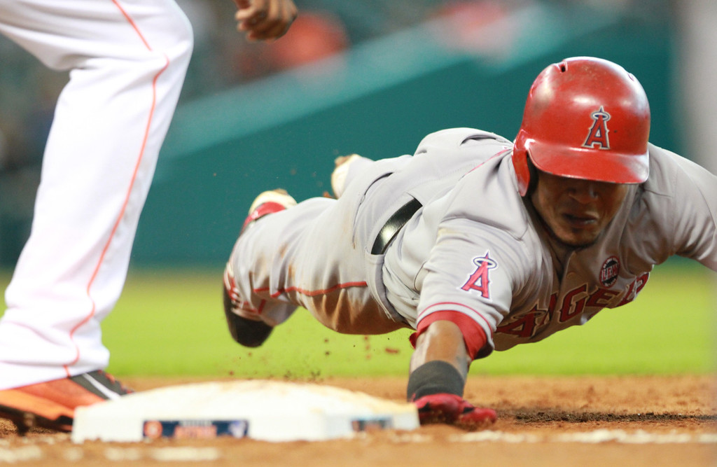 . HOUSTON, TX- SEPTEMBER 15: Erick Aybar #2 of the Los Angeles Angels of Anaheim dives safely back to first base against the Houston Astros in the fourth inning on September 15, 2013 at Minute Maid Park in Houston, Texas. (Photo by Thomas B. Shea/Getty Images)