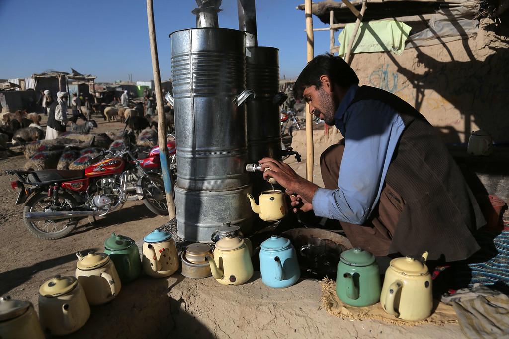 . An Afghan man prepares tea for his customers at a livestock market ahead of the sacrificial Eid al-Adha festival in Ghazni on October 1, 2014. Muslims across the world are preparing to celebrate the annual festival of Eid al-Adha, or the Festival of Sacrifice, which marks the end of the Hajj pilgrimage to Mecca and commemorates Prophet Abraham\'s readiness to sacrifice his son to show obedience to God. Rahmatullah Alizadah/AFP/Getty Images