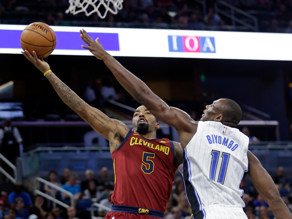 . Cleveland Cavaliers\' J.R. Smith (5) shoots as Orlando Magic\'s Bismack Biyombo (11) defends during the first half of an NBA preseason basketball game, Friday, Oct. 13, 2017, in Orlando, Fla. (AP Photo/John Raoux)