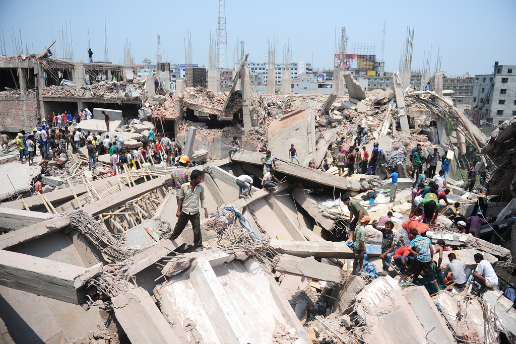 . Bangladeshi civilian volunteers assist in rescue operations after an eight-story building collapsed in Savar, on the outskirts of Dhaka, on April 24, 2013.  AFP PHOTO/Munir uz ZAMAN/AFP/Getty Images
