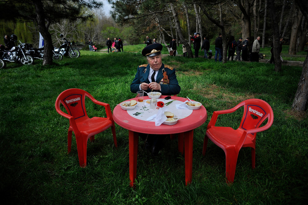 . A WWII veteran sits at a table during a celebration of the 70th anniversary of the liberation of Simferopol, Crimea, Sunday, April 13, 2014. On Sunday, residents of Simferopol mark the 70th anniversary of liberation of Simferopol from German troops during World War II. (AP Photo/ Andrew Lubimov)