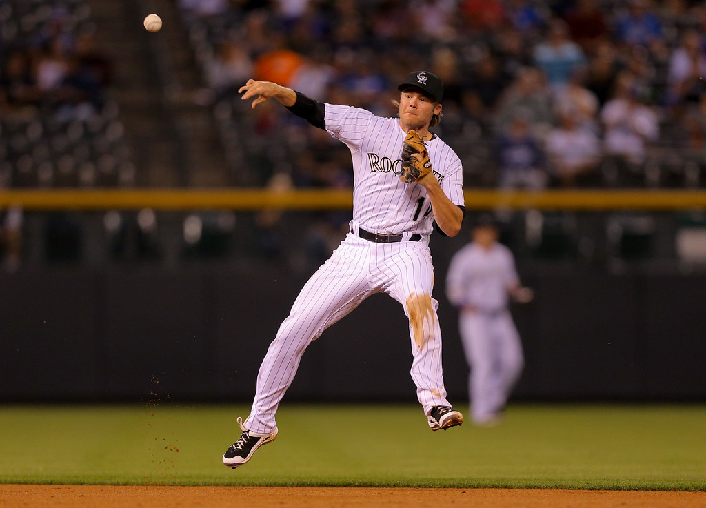 . DENVER, CO - SEPTEMBER 16:  Shortstop Josh Rutledge #14 of the Colorado Rockies makes an off-balance throw to first base for the first out of the third inning against the Los Angeles Dodgers at Coors Field on September 16, 2014 in Denver, Colorado. (Photo by Justin Edmonds/Getty Images)