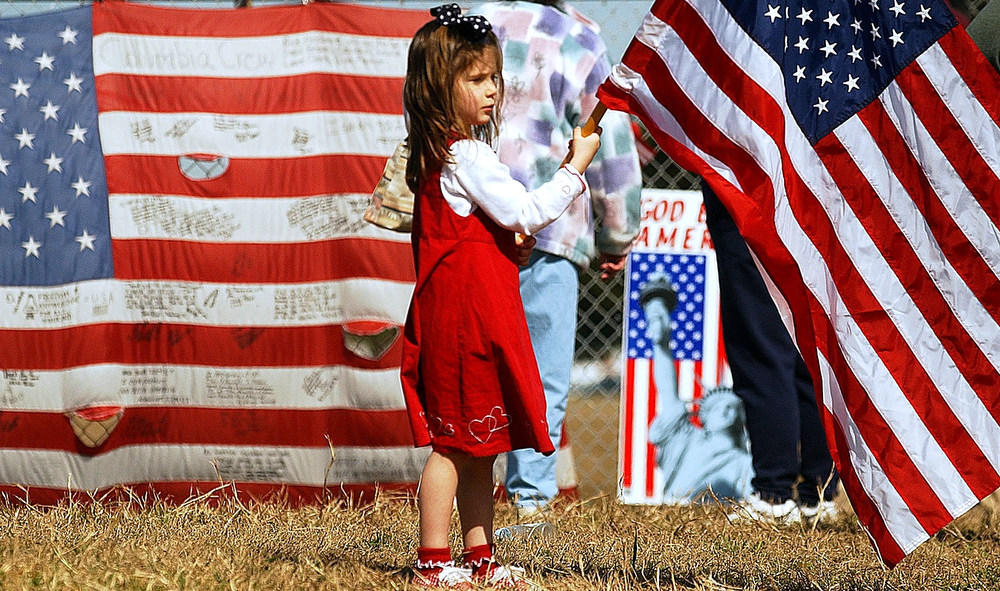 . LYNDON B. JOHNSON SPACE CENTER HOUSTON, TEXAS 4-year-old Morgan Smith of Kingwood, Texas holds an American flag after the memorial service for space shuttle Columbia astronauts  with President Bush inside the center on Tuesday, February 4, 2003. She was outside at the entrance gate. CYRUS MCCRIMMON, The denver Post