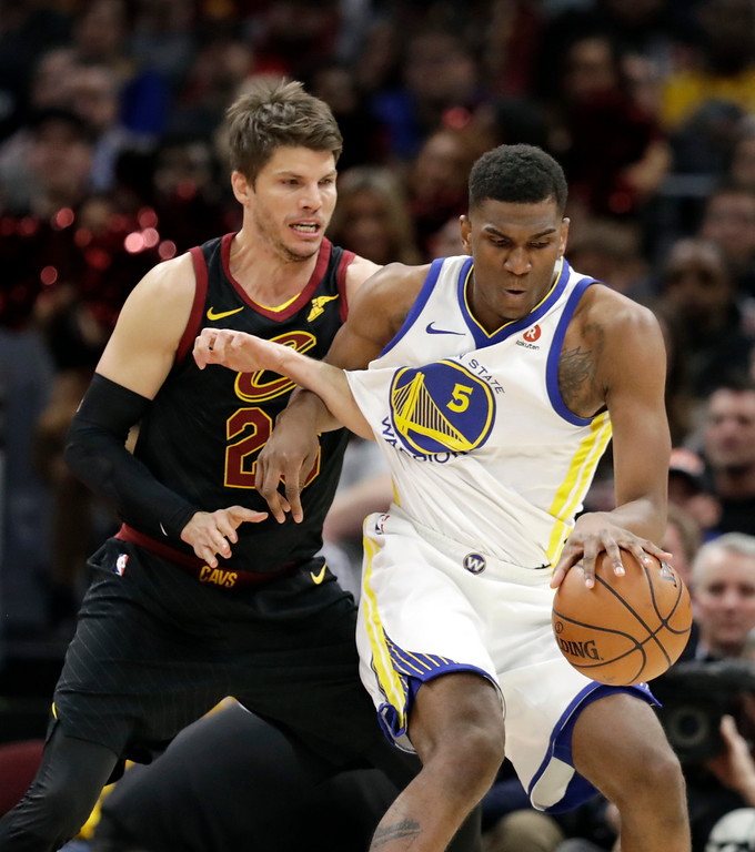 . Golden State Warriors\' Kevon Looney, right, drives past Cleveland Cavaliers\' Kyle Korver in the first half of an NBA basketball game, Monday, Jan. 15, 2018, in Cleveland. (AP Photo/Tony Dejak)
