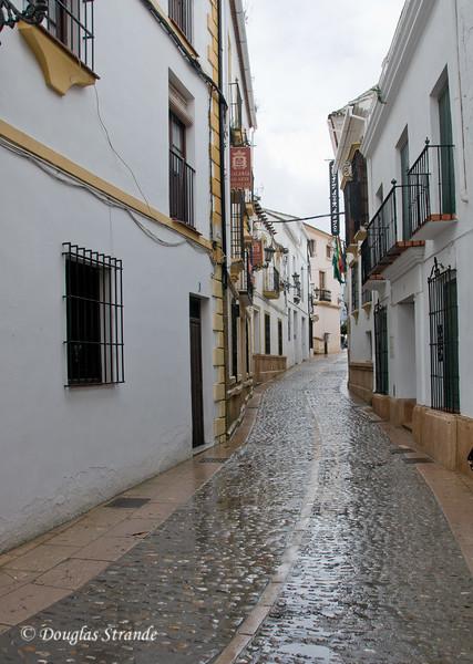 Mon 3/14 in Ronda: Narrow street with wet cobblestones