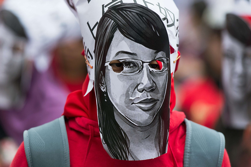 """. A migrant worker wears a mask resembling a likeness of former Indonesian maid Erwiana Sulistyaningsih during a Labour Day rally in Hong Kong on May 1, 2014. Over a thousand protesters gathered for the annual May Day rally in Hong Kong\'s landmark Victoria Park to walk towards the government headquarters waving colourful flags and placards, while singing a Chinese version of the famous \""""Do you hear the people sing?\"""" from the musical Les Miserables, calling for better working conditions and better wages.  (ANTHONY WALLACE/AFP/Getty Images)"""