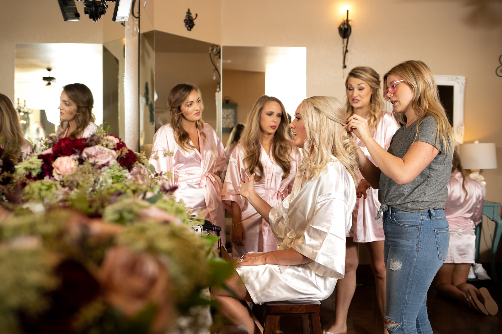 a bride getting ready for her wedding with her bridesmaids standing around her talking wearing matching pink robes