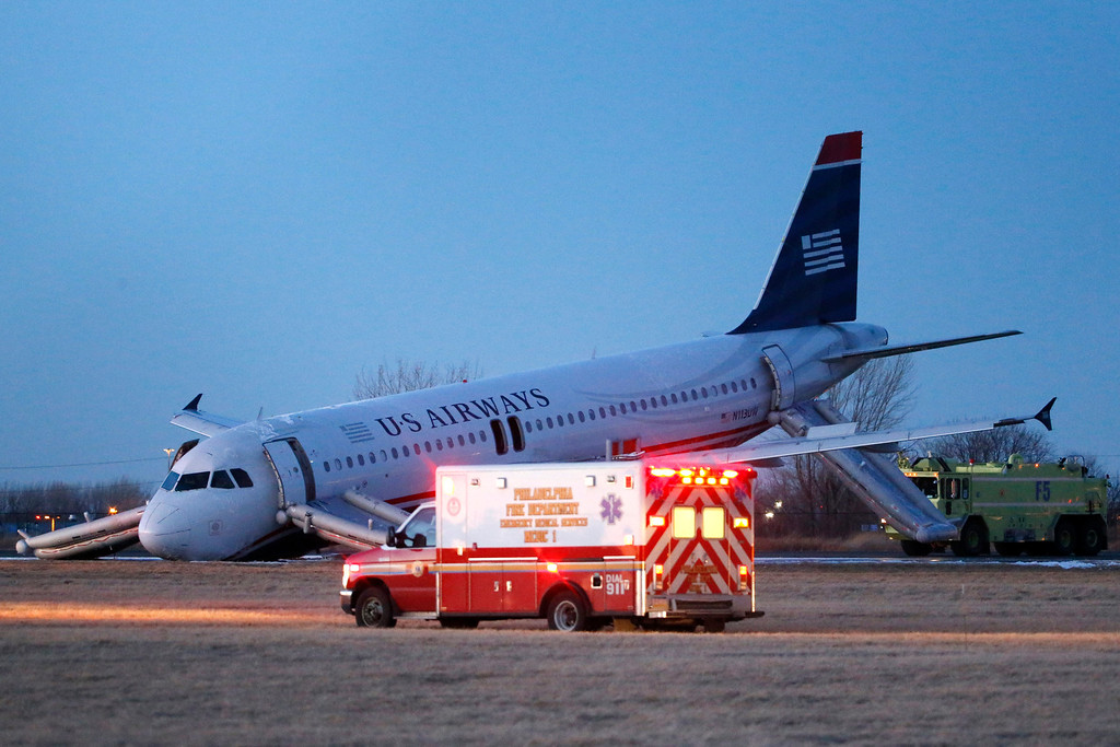 . Emergency vehicles drive past a damaged US Airways jet at the end of a runway at the Philadelphia International Airport, Thursday, March 13, 2014, in Philadelphia. Airline officials said the flight was heading to Fort Lauderdale, Fla., when the pilot was forced to abort takeoff around 6:30 p.m., after the front landing gear failed. An airport spokeswoman said no injuries have been reported. (AP Photo/Matt Slocum)