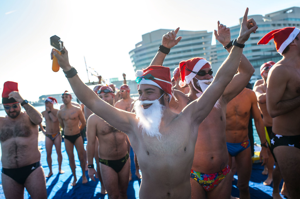 . Competitors in fancy dress enjoy the atmosphere prior to the 105th Barcelona Traditional Christmas Swimming Cup at the Old Harbor of Barcelona on December 25, 2014 in Barcelona, Spain. The Copa Nadal is organized by the Barcelona Swimming Club and involves competitors swimming across some 200 meters of water in the harbor. Launched in 1908 the event has only been suspended three times when the Spanish Civil War interrupted proceedings between 1936 and 1938.  (Photo by David Ramos/Getty Images)