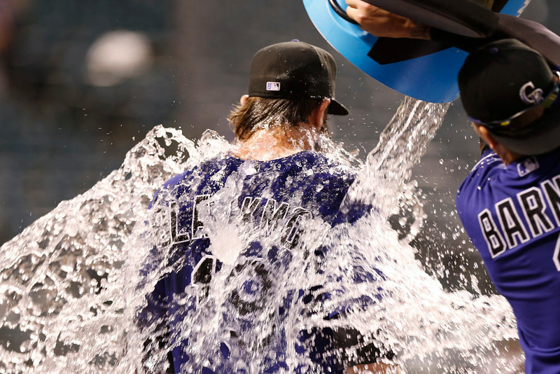 . While doing a standup interview for televison, Colorado Rockies\' Charlie Blackmon, left, is doused by teammate Brandon Barnes after Blackmon\'s walkoff, RBI-single against the San Francisco Giants in the ninth inning of the Rockies\' 10-9 victory in a baseball game in Denver on Monday, Sept. 1, 2014. (AP Photo/David Zalubowski)