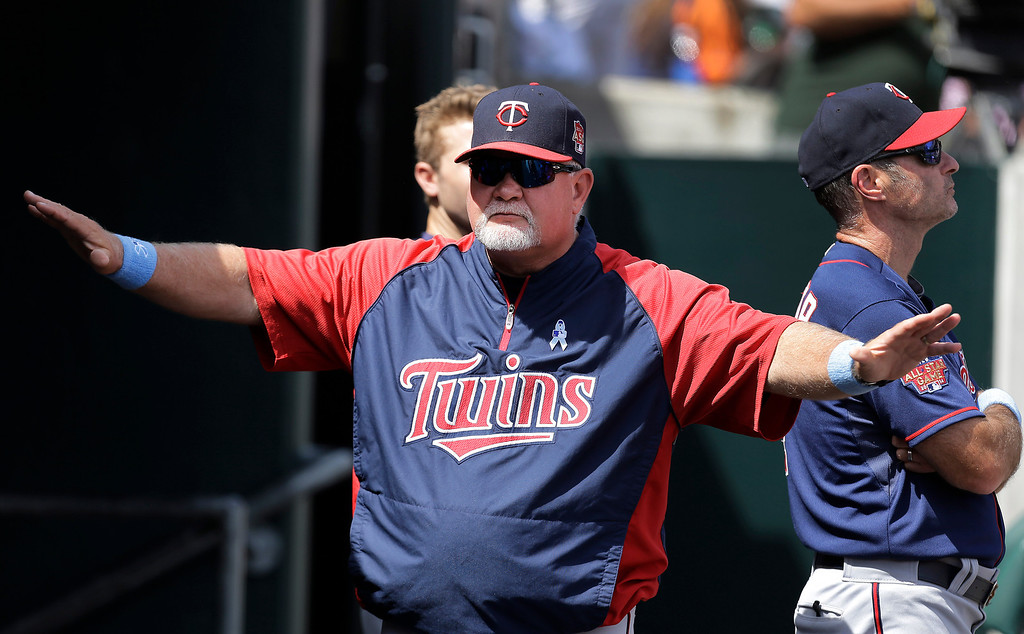 . Minnesota Twins manager Ron Gardenhire signals safe during a review of a Brian Dozier ground out on a bunt against the Detroit Tigers in the eighth inning of a baseball game in Detroit, Sunday, June 15, 2014. Dozier was called out on the play and after review was upheld. (AP Photo/Paul Sancya)