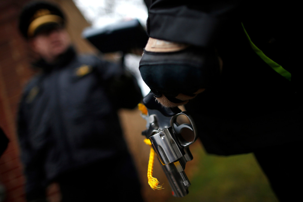 . An Evanston police officer holds a  firearm that was turned in as part of an amnesty-based gun buyback program in Evanston, Illinois December 15, 2012. Residents were given $100 for each operational firearm given in, and no criminal charges would be laid.    REUTERS/Jim Young