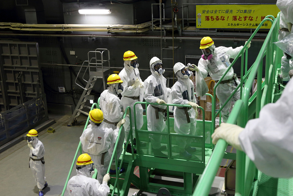 . Members of the media and Tokyo Electric Power Co. employees wearing protective suits and masks walk up the steps of a spent fuel handling machine as they look at the spent fuel pool inside the building housing the Unit 4 reactor at the Fukushima Dai-ichi nuclear power plant in Okuma, Fukushima, northeastern Japan, Thursday, Nov. 7, 2013. Japanese regulators on Oct. 30 formally approved the removal of fuel rods from the cooling pool at the damaged Unit 4 reactor building considered the highest risk at the crippled nuclear plant. Removing the fuel rods is the first major step in a decommissioning process that is expected to last decades at the Fukushima plant, where three reactors melted down after the March 2011 earthquake and tsunami. (AP Photo/Tomohiro Ohsumi, Pool)