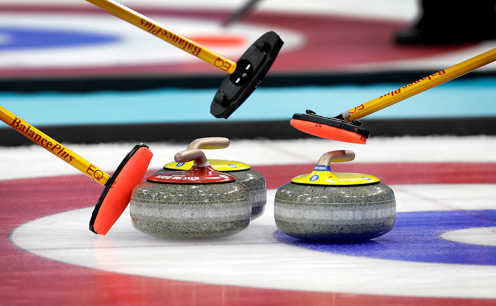 . China\'s women\'s curling team use their brooms to point at the rocks as they strategise their next move during the women\'s curling competition against the United States at the 2014 Winter Olympics, Wednesday, Feb. 12, 2014, in Sochi, Russia. (AP Photo/Wong Maye-E)