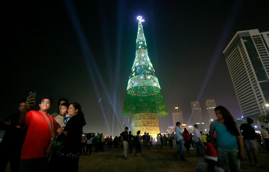 . A Sri Lankan family takes photographs standing near an enormous artificial Christmas tree as others gather around it in Colombo, Sri Lanka, Saturday, Dec. 24, 2016. Sri Lanka has unveiled a towering Christmas tree, claiming to have surpassed the world record for the tallest artificial Christmas tree. (AP Photo/Eranga Jayawardena)