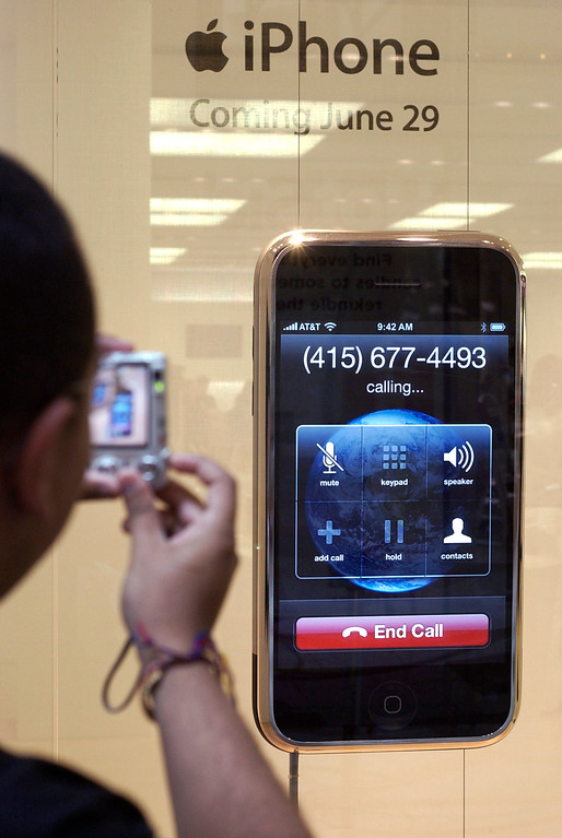 . Antonio Copete, of Cambridge, Mass., takes a photograph of a window display of the new Apple iPhone at an Apple store, Friday, June 29, 2007 at the CambridgeSide Galleria in Cambridge, Mass. The new iPhone is scheduled to go on sale later today. (AP Photo/Lisa Poole)