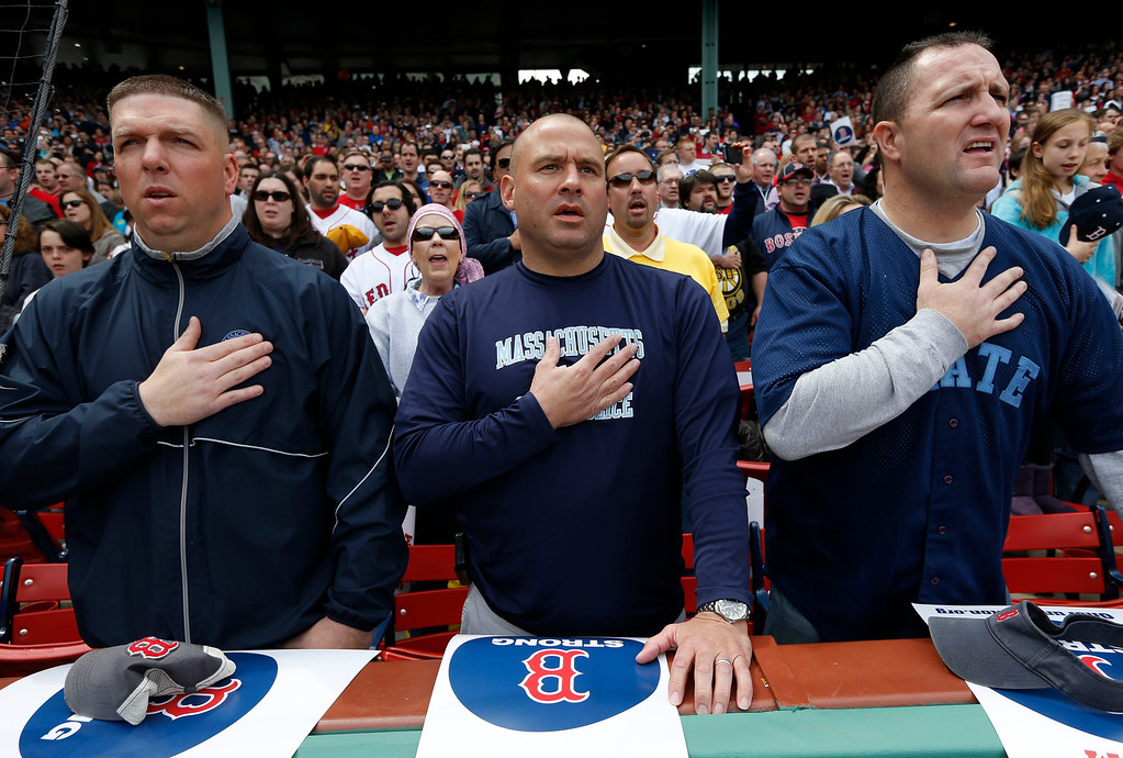 . Three members of the Massachusetts State Police place their hands over their heart during the national anthem before a baseball game between the Boston Red Sox and the Kansas City Royals in Boston, Saturday, April 20, 2013. (AP Photo/Michael Dwyer)