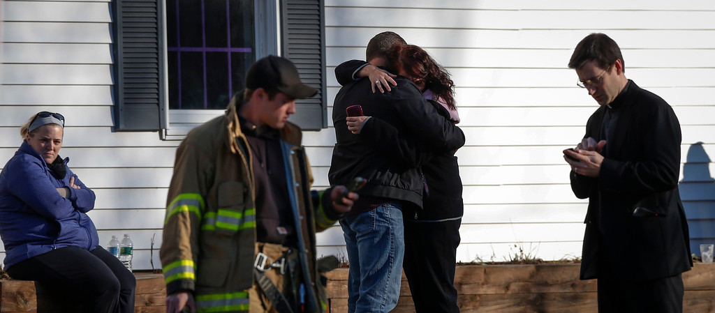 . Family members embrace near Sandy Hook Elementary School, where a gunman opened fire on school children and staff in Newtown, Connecticut December 14, 2012. A heavily armed gunman opened fire on school children and staff at a Connecticut elementary school on Friday, killing at least 26 people, including 18 children, in the latest in a series of shooting rampages that have tormented the United States this year.     REUTERS/Adrees Latif