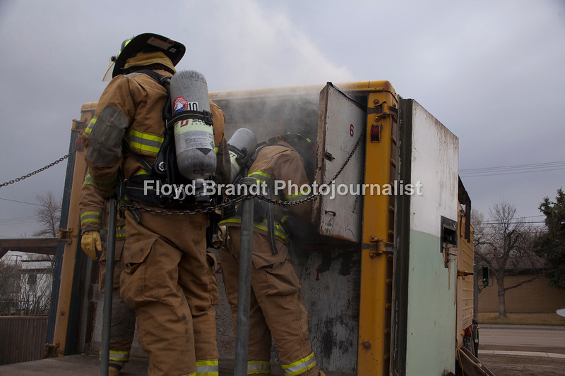 "Havre Daily News/Floyd Brandt  Smoke poured out of a trailer parked at the Havre Fire Department where Firefighter Chris Cox enters the Confined Space Training trailer Monday Austin Shupe waits and watches for his turn at finding his way through the small space. The traing helps the firefighters prepare themselves for entering a fire that may be very confining and dangerous. Assisant Fire Chief Kelly Jones said that it gives his firefighters a chance to get use to their equipment and gear in small spaces and to look out for hazards. For Chris Cox, ""It was tight and you can't see anything but it was a lot of fun,"" he said."