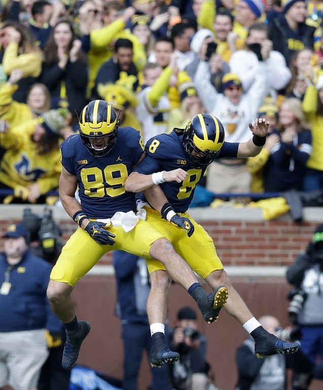 . Michigan quarterback John O\'Korn (8) and tight end Ian Bunting (89) celebrate after a 2-yard touchdown by Khalid Hill during the first half of an NCAA college football game against Ohio State, Saturday, Nov. 25, 2017, in Ann Arbor, Mich. (AP Photo/Carlos Osorio)0
