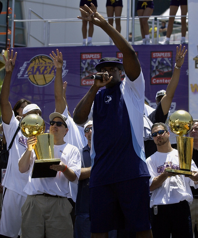. Los Angeles Lakers\' Shaquille O\'Neal holds up four fingers along with other members of the Lakers organization as O\'Neal leads a chant for a fourth victory during the Lakers\' celebration of their third consecutive NBA championship Friday, June 14, 2002, in downtown Los Angeles. (AP Photo/Mark J. Terrill)