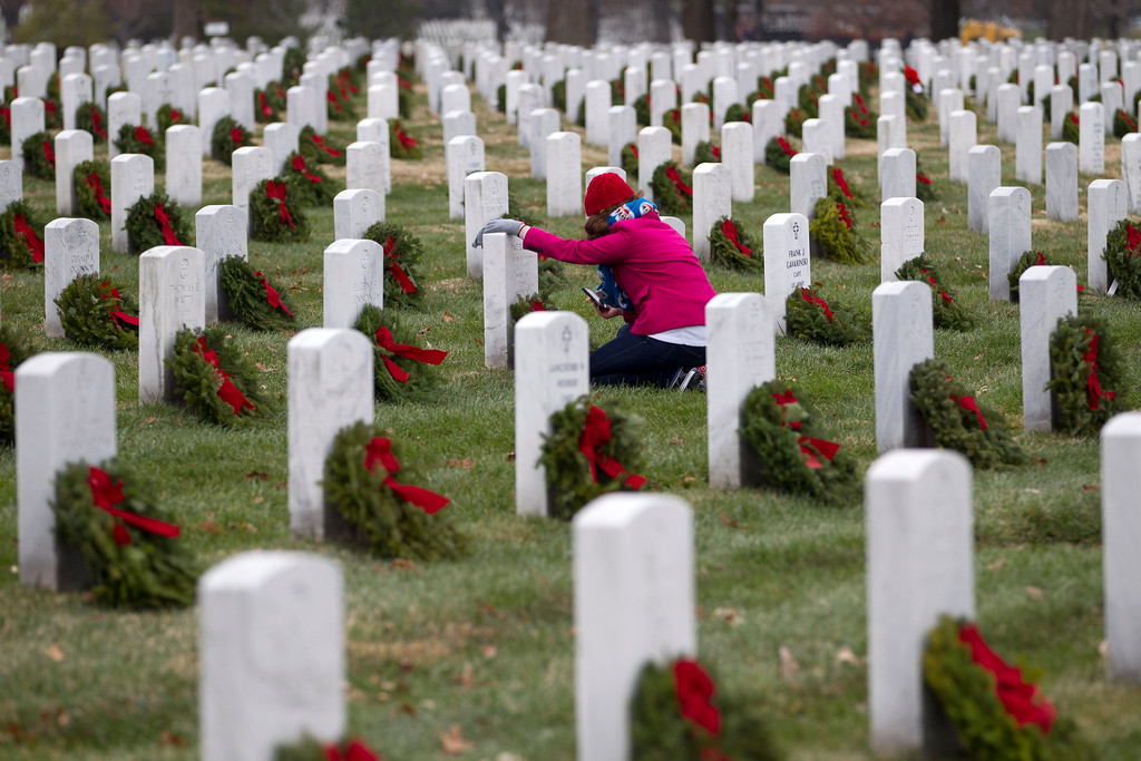 . Volunteer Brandi Besecker lay a holiday wreaths at the grave of her aunt at Arlington National Cemetery in Arlington, Va., Saturday Dec. 14, 2013, during Wreaths Across America Day. Wreaths Across America was started in 1992 at Arlington National Cemetery by Maine businessman Morrill Worcester and has expanded to hundreds of veterans\' cemeteries and other locations in all 50 states and beyond. (AP Photo/Jose Luis Magana)