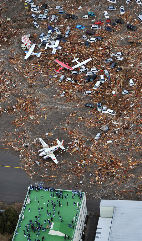 . People seek refuge on the rooftop of a building as light planes and vehicles sit among the debris after they were swept by a tsunami that struck Sendai airport in northern Japan on Friday March 11, 2011. A magnitude 8.9 earthquake slammed Japan\'s eastern coast Friday, unleashing a 13-foot (4-meter) tsunami that swept boats, cars, buildings and tons of debris miles inland.  (AP Photo/Kyodo News)