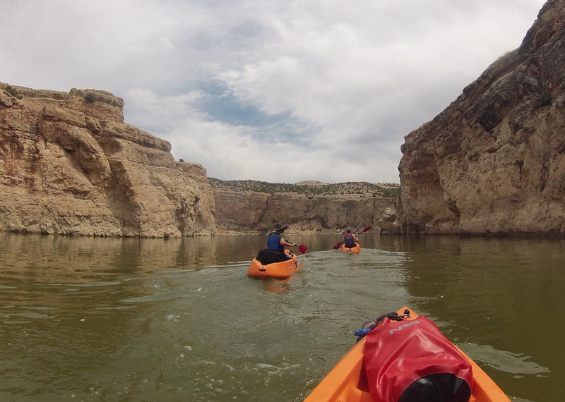 Kayakers passing through a narrow passage way on a Bighorn Canyon kayak tour