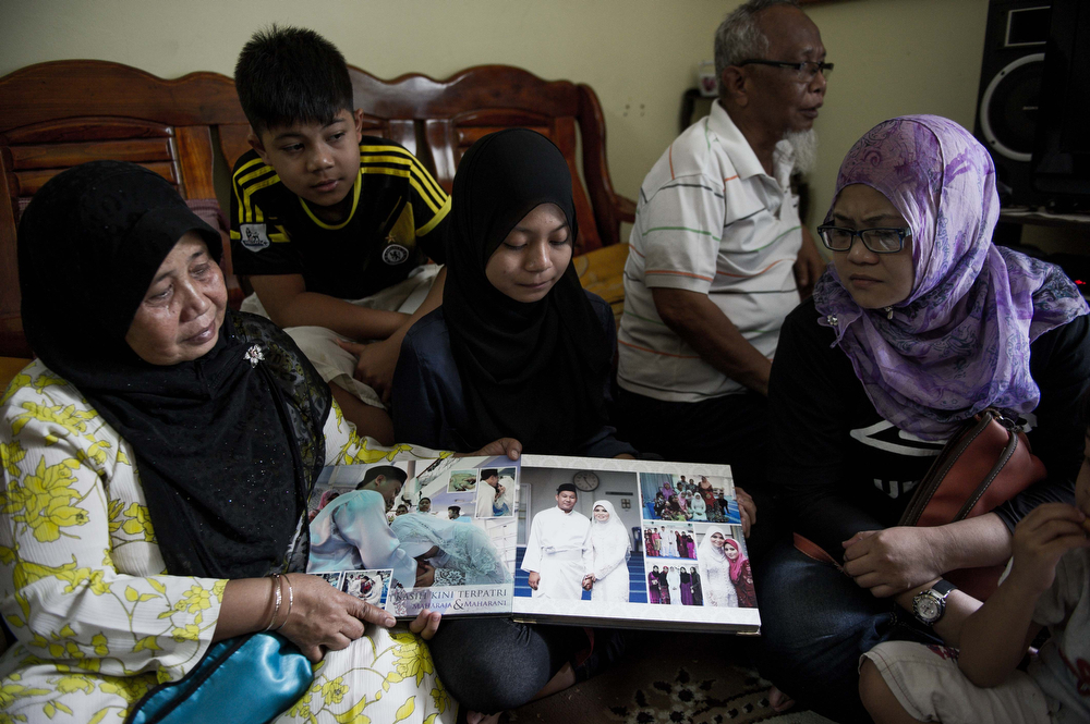 . Family members look at a wedding album of Norliakmar Hamid and Razahan Zamani, passengers on a missing Malaysia Airlines Boeing 777-200 plane in Kuala Lumpur on March 8, 2014. Malaysia and Vietnam on March 8 led a search for a Malaysia Airlines jet that has gone missing over Southeast Asia, as fears mounted over the fate of the 239 people aboard.  (MOHD RASFAN/AFP/Getty Images)