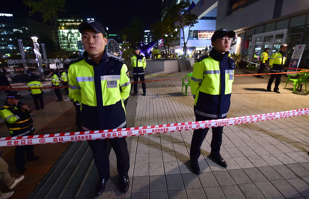 . Policemen stand guard near a broken ventilation grate after concert goers fell through it into an underground parking area below in Seongnam City, south of Seoul, on October 17, 2014.  AFP PHOTO / JUNG YEON-JE/AFP/Getty Images