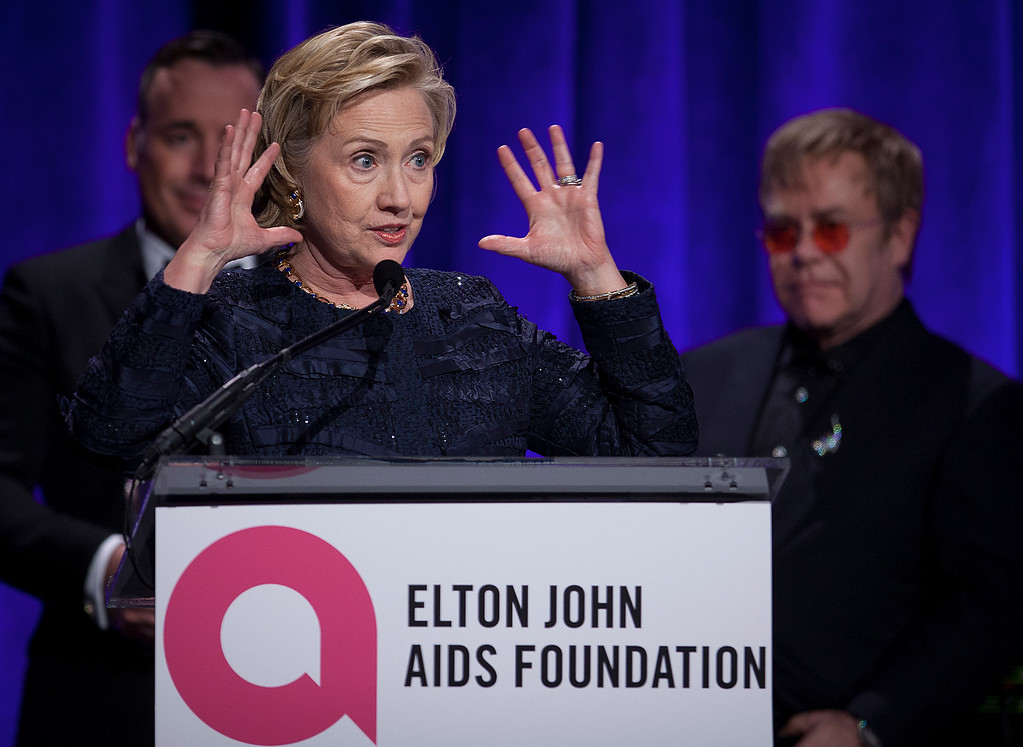 """. Former Secretary of State Hillary Clinton speaks as Elton John, right, and his partner David Furnish, rear, look on, after receiving her Founders award during the Elton John AIDS Foundation\'s 12th Annual \""""An Enduring Vision\"""" benefit gala at Cipriani Wall Street on Tuesday, Oct. 15, 2013, in New York. (Photo by Carlo Allegri/Invision/AP)"""