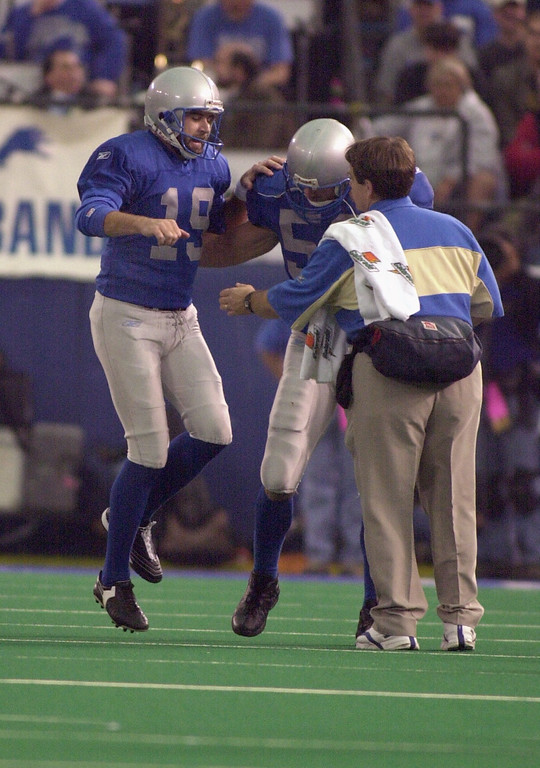 . Detroit Lions punter John Jett (left,#19) is helped off the field by an unidentified teammate and personnel member, after getting hurt against the Green Bay Packers, Thursday, November 22, 2001, at the Silverdome in Pontiac, Mich.