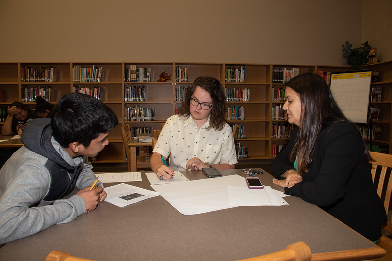 Jonathan Maul (middle) and Mara Barbosa with a West Oso High School student at the Spanish event at the library.