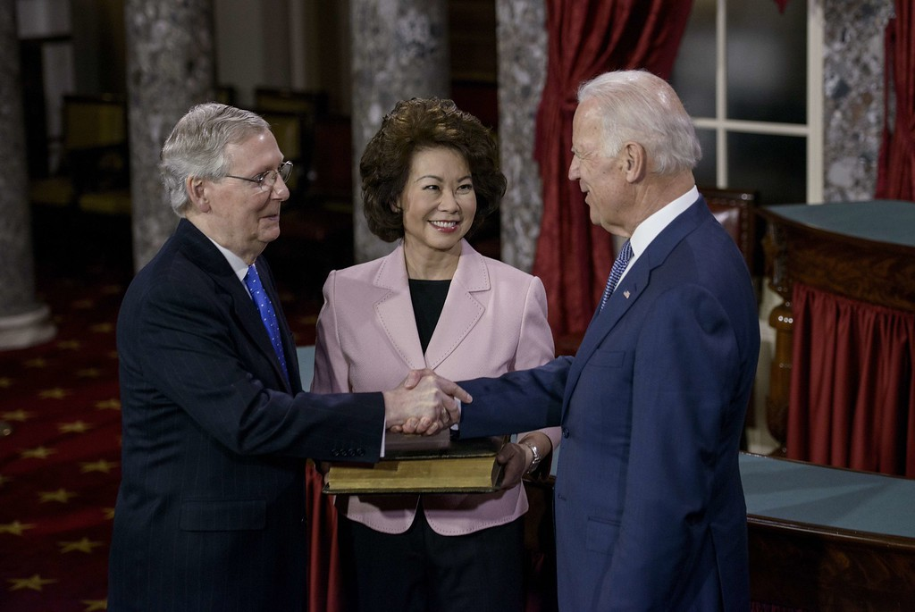. Elaine Chao (C) watches as her husband Senate Majority Leader Senator Mitch McConnell (R-KY) and US Vice President Joseph R. Biden(R) participate in a mock swearing-in in the Old Senate Chamber on Capitol Hill January 6, 2015 in Washington, DC. The 114th Congress convened today with Republicans taking majority control of both the Senate and House of Representatives. BRENDAN SMIALOWSKI/AFP/Getty Images