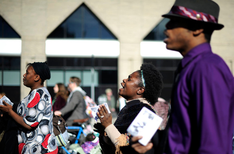 . DLarea Edwards, center, and Yves Rhone II , right, sing with a group from the Rapture Missionary Baptist Church as  they walk in the  Martin Luther King Jr. Marade  as it winds along E. Colfax Ave. on it\'s way downtown.  The marade, march/parade,  started at the MLK statue in the City Park on Monday, January 21, 2013.   (Photo By Cyrus McCrimmon / The Denver Post)