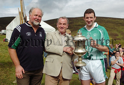Nicky Brennan President of the GAA presenting the All Ireland Poc Fada  trophy to  Brendan Cummins of Tipperary with Martin Donnelly sponsor on left