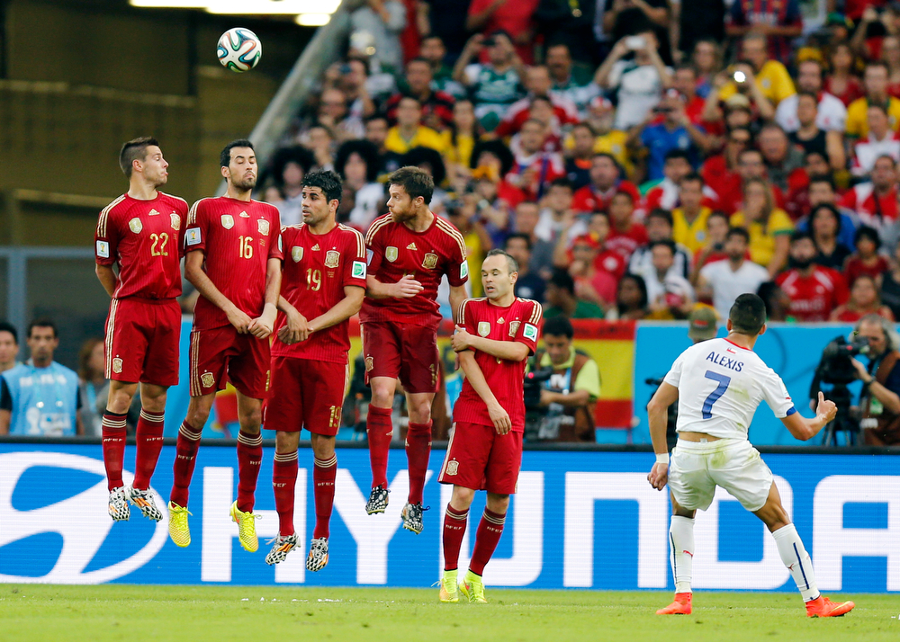 . Chile\'s Alexis Sanchez takes a free kick over Spain\'s defensive wall during the group B World Cup soccer match between Spain and Chile at the Maracana Stadium in Rio de Janeiro, Brazil, Wednesday, June 18, 2014.  (AP Photo/Frank Augstein)