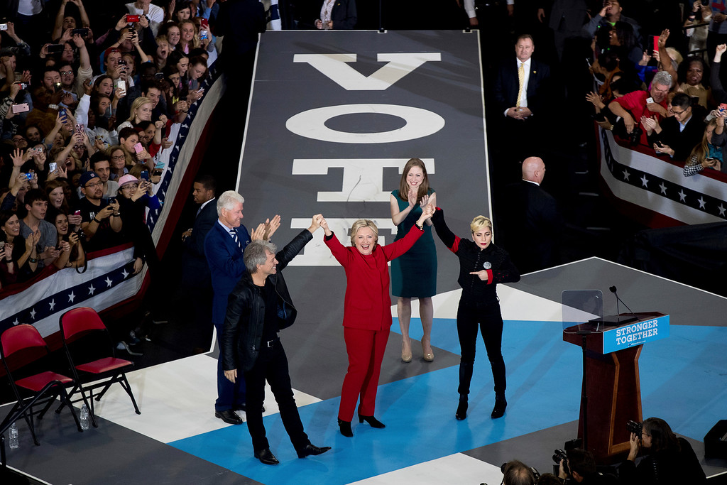 . Democratic presidential candidate Hillary Clinton, center, reacts to the audience as she was surrounded by Jon Bon Jovi, from left, clockwise, her husband, former president Bill Clinton, their daughter Chelsea Clinton and Lady Gaga during a campaign rally in Raleigh, N.C., Tuesday, Nov. 8, 2016. (AP Photo/Gerry Broome)