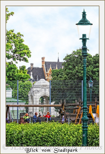 The View from the Stadtpark Playgrounds, the Jugendstil entrance gate to the Wienfluss promenade, then behind that the Akademisches Gymnasium, founded 1553 [the building was constructed in 1886 in neo-Renaissance style]