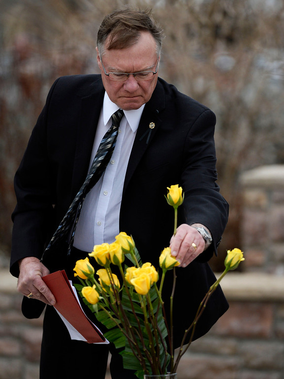 . Executive director of the Colorado Department of Corrections, Rick Raemisch, places a yellow rose in a vase honoring Tom Clements at the Colorado Department of Corrections Fallen Officer Memorial  at the Territorial Correctional Facility park Saturday morning, March 15, 2014. (Photo By Andy Cross / The Denver Post)