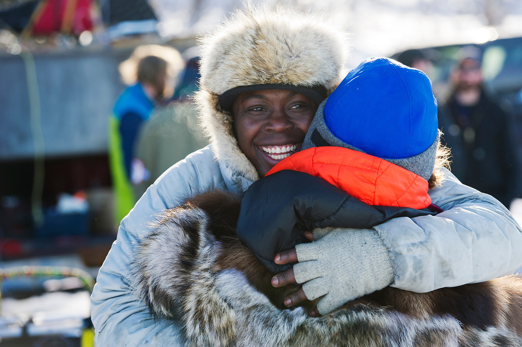 . Musher Newton Marshall, who said he\'s celebrating his 31st birthday, hugs someone before the start of the Iditarod Trail Sled Dog Race on Sunday, March 2, 2014, in Willow, Alaska. (AP Photo/Anchorage Daily News, Marc Lester)