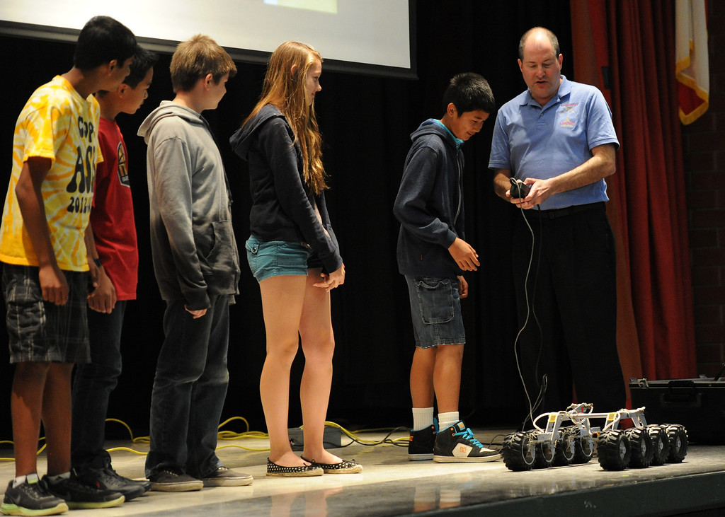 . (John Valenzuela/Staff Photographer)  Brian Cooper, lead rover driver of Curiosity, shows eight graders from Cope Middle School in Redlands a small robot version of a rover during his visit on Friday, April 19, 2013.  Cooper is the worlds first Mars rover driver and has worked on every rover mission sent to Mars.