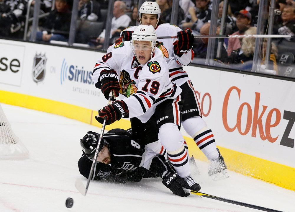 Description of . Chicago Blackhawks Jonathan Toews (C) and Daniel Carcillo fight for the puck with Los Angeles Kings Drew Doughty during the first period of their NHL hockey game in Los Angeles, California, January 19, 2013. REUTERS/Lucy Nicholson