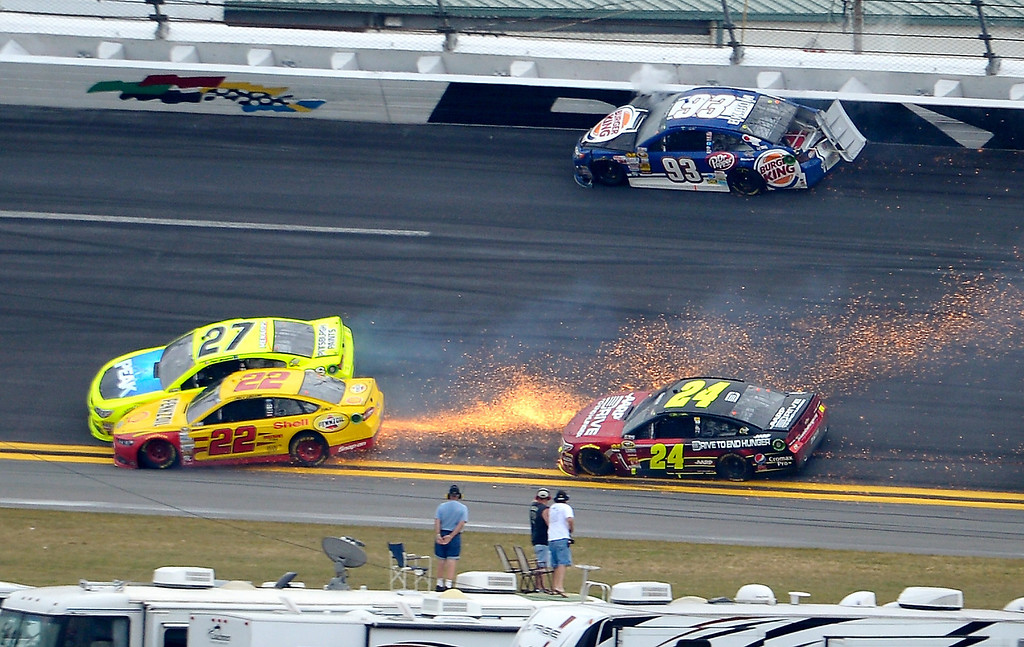 . Travis Kvapil (93) hits the wall as Paul Menard (27) and Joey Logano (22) collide, sending sparks on Jeff Gordon (24), between Turns 1 and 2 on the final lap of the NASCAR Daytona 500 Sprint Cup Series auto race at Daytona International Speedway in Daytona Beach, Fla., Sunday, Feb. 24, 2013. (AP Photo/Phelan M. Ebenhack)