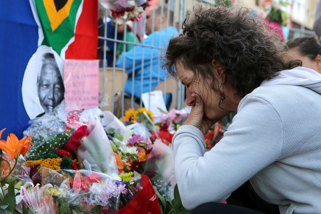 . TOPSHOTS  A woman cries after placing flowers in front of a picture of late South African former president Nelson Mandela during an inter-faith service on December 6, 2013, held at the Grand Parade in Cape Town, where Mandela made his first speech as a free man in 1990. Mandela, the revered icon of the anti-apartheid struggle in South Africa and one of the towering political figures of the 20th century, died in Johannesburg on December 5 at age 95. Mandela, who was elected South Africa\'s first black president after spending nearly three decades in prison, had been receiving treatment for a lung infection at his Johannesburg home since September, after three months in hospital in a critical state.  /AFP PHOTO/JENNIFER BRUCEJENNIFER BRUCE/AFP/Getty Images