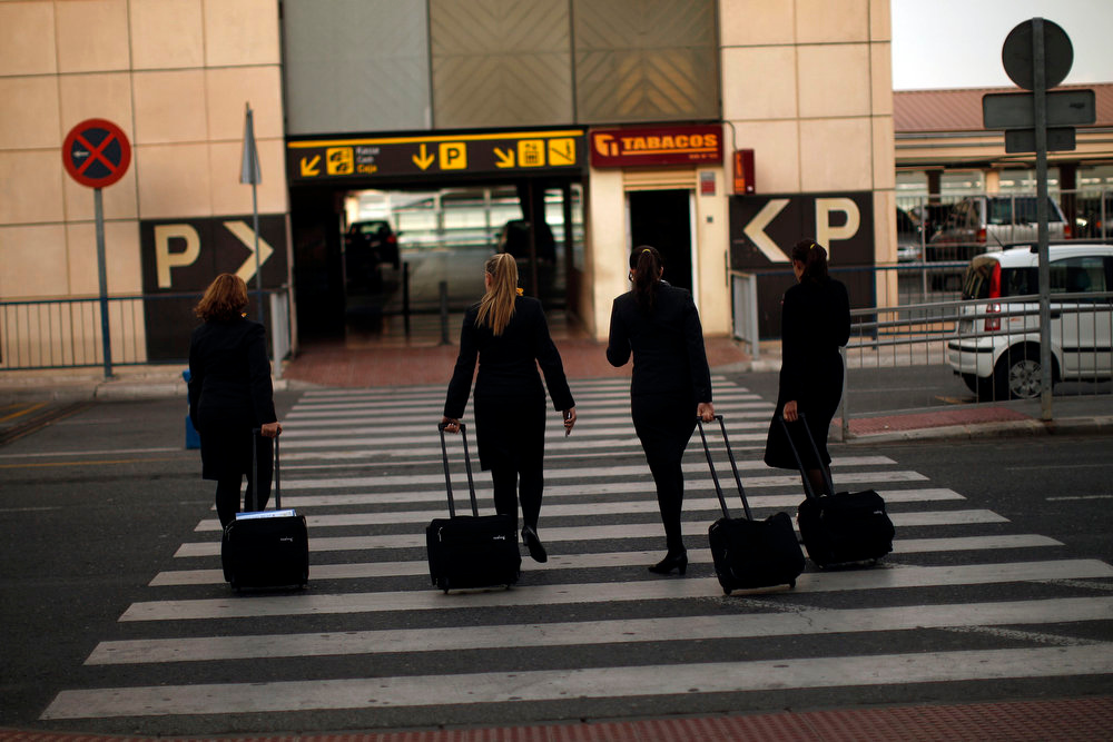 . Vueling Airlines stewardesses pull their suitcases as they leave the Pablo Ruiz Picasso Airport during a strike of Iberia workers in Malaga, southern Spain February 18, 2013. Striking union workers clashed with police at Madrid\'s Barajas airport on Monday on the first day of a week-long strike over more than 3,800 pending job cuts at Spain\'s flagship airline Iberia. REUTERS/Jon Nazca